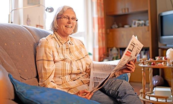 Bewohnerin liest Zeitung in ihrem Einzelzimmer im Pflegewohnstift Hamburg