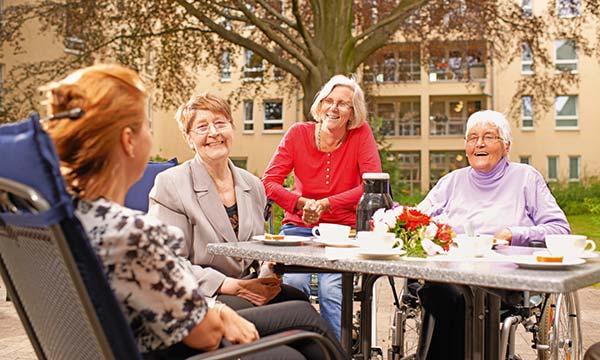 Bewohnerinnen sitzen im Garten im Pflegewohnstift Hamburg