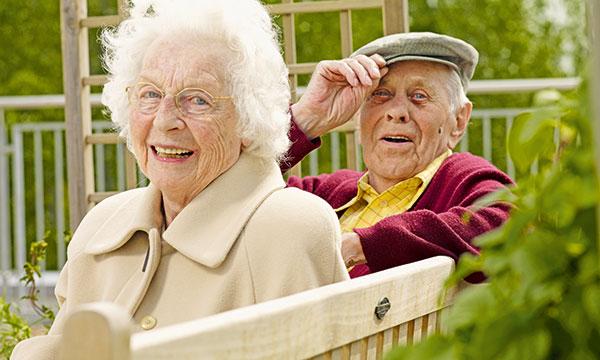 Bewohner-Paar sitzt im Garten vom Pflegewohnstift Falkensee