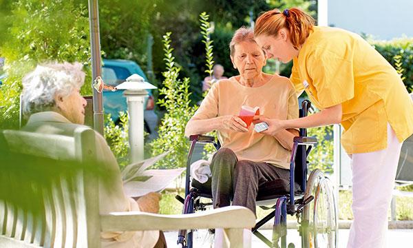 Bewohnerinnen und Pflegefachkraft auf Terrasse am Altenheim Frankfurt