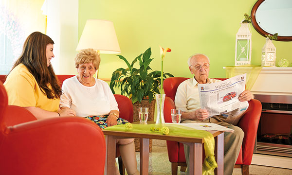 Bewohner-Pärchen mit Pflegefachkraft auf dem Sofa im Pflegeheim Garbsen