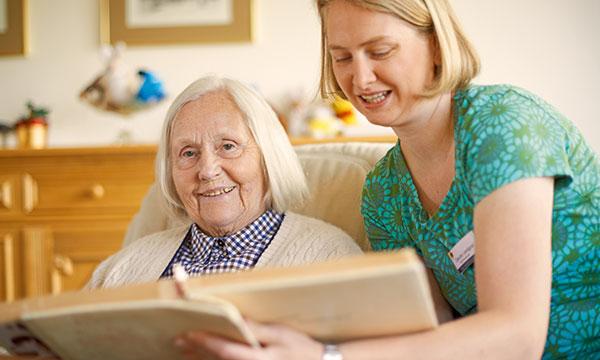 Bewohnerin bekommt etwas in ihrem Zimmer vorgelesen im Pflegeheim in Hamburg
