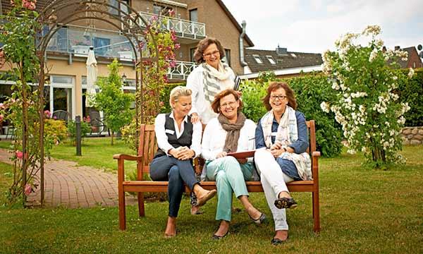 Mitarbeiter sitzen auf der Bank im Garten des Pflegeheim in Hamburg