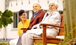 Plfegekraft und Bewohner-Pärchen sitzen auf der Bank vor dem Pflegewohnstift Leipzig