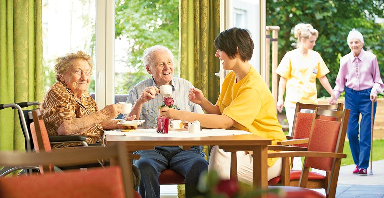 Bewohnerpaar sitzen mit Pflegekraft im Pflegeheim Leipzig