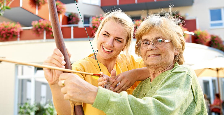 Bewohnerin und Pflegefachkraft beim Bogenschießen vor dem Pflegeheim Leipzig