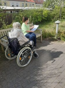 Geschichten vorlesen, Pflegerin ließt den Bewohnern was vor