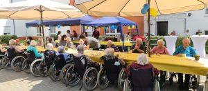 Sommerfest im Pflegewohnstift am Wasserturm. Bewohner sitzen zusammen