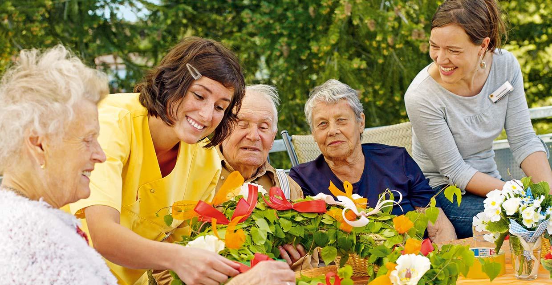 Bewohnerin & Angestellte beim Übergeben eines Blumenkranzes im Altenheim