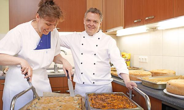 Angestellte und Koch bei der Essensvergabe